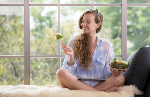 Healthy young woman sitting on a couch using tablet and holding a salad bowl looking relaxed and comfortable