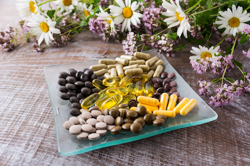 plate of pills with chamomile flowers