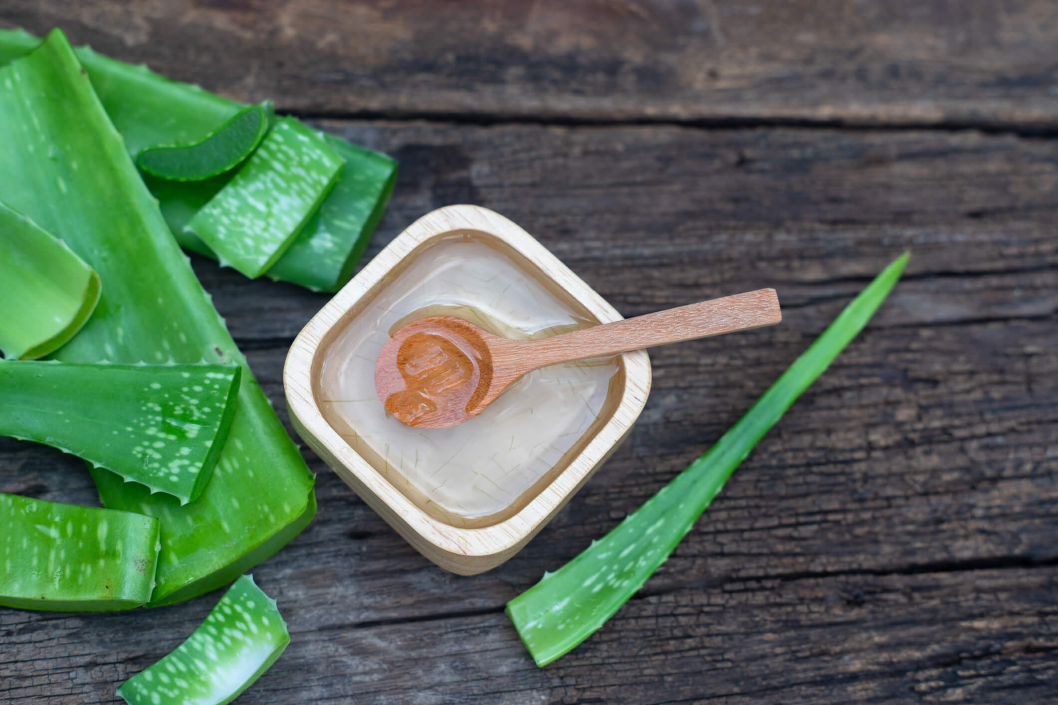 aloe vera stem and gel on wooden table