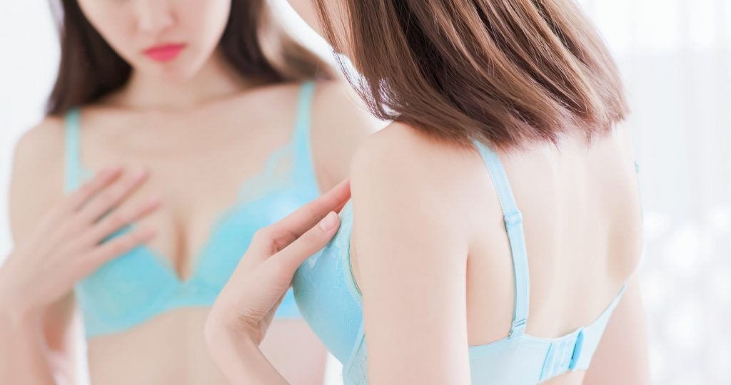 woman checking for any unusual breast changes