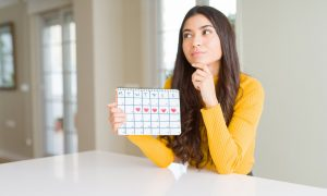 woman holding menstruation calendar pondering irregular periods