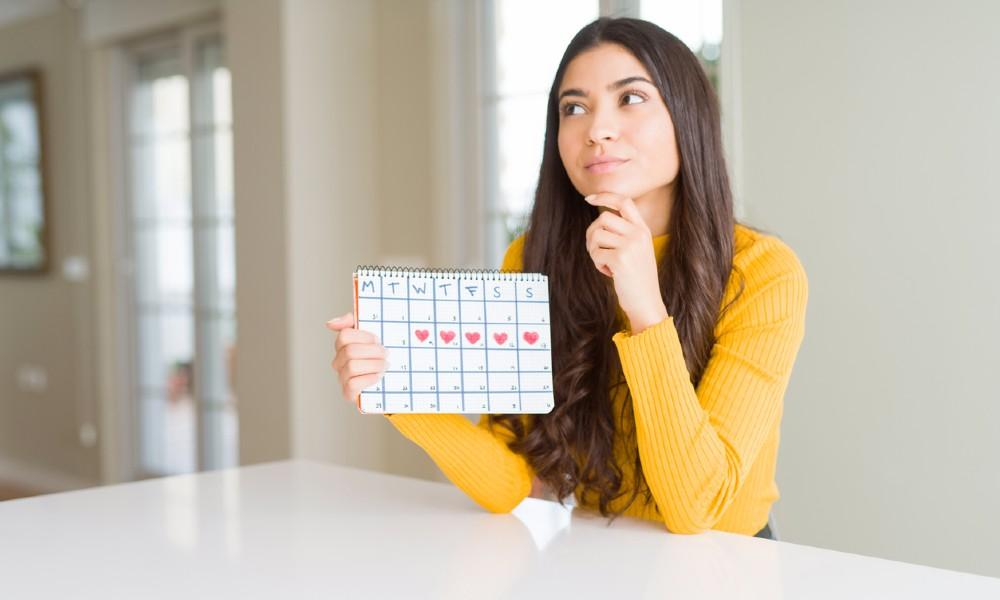 woman holding menstruation calendar pondering irregular periods