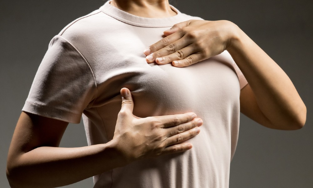 woman checking herself for fibrocystic breast disease symptoms