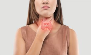 Woman with hypothyroidism symptoms touching her neck.