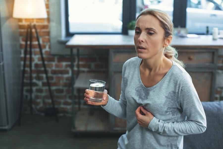 Woman experiencing menopausal symptoms as how long does menopause last