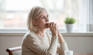 """A woman sits with a thoughtful look, wondering: """"how long does menopause last?"""