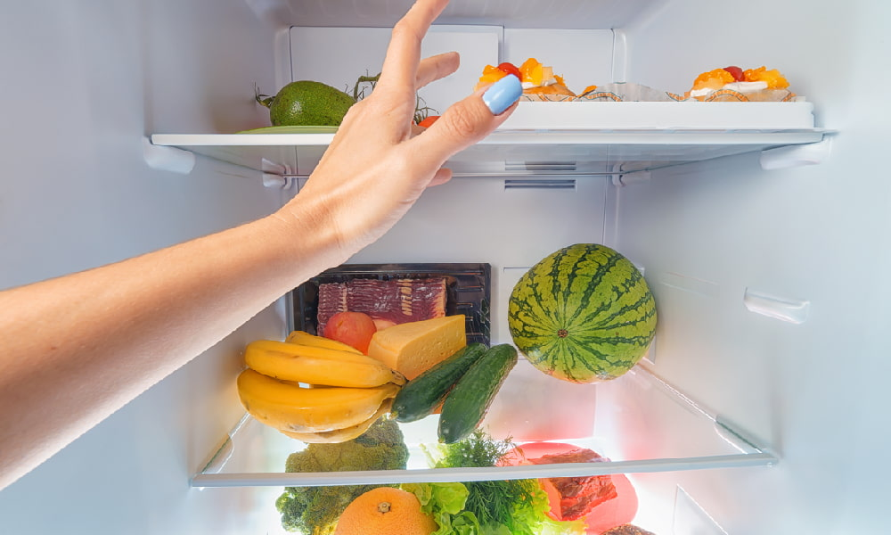A woman's hand reaches into an open fridge full of fresh produce such as fruits and other items, some of which may not be part of an elimination diet.