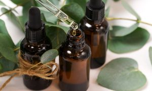 Brown glass essential oil bottles with an eyedropper and eucalyptus leaves with twine signify the benefits of essential oils.