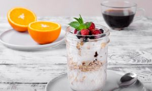 An image of a healthy breakfasts of overnight oats topped with fresh berries in a jar