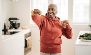 A senior woman with health concerns takes some preventive measures by exercising in her bedroom with weights.
