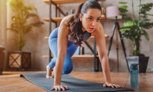 A dark-haired woman in blue sport clothes practices yoga poses on a gray mat with a water bottle nearby.