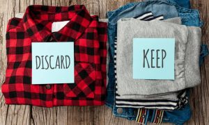 Two stacks of folded clothes labeled keep and discard to declutter for mental health
