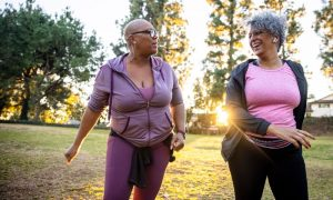 Two Black women wearing athleisure-style clothing go for a walk out in nature to get some low impact exercise.