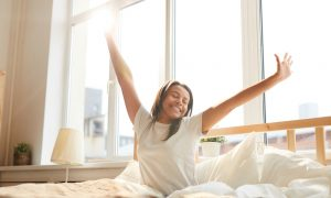 A young female morning person wakes up by happily stretching in the morning sun.