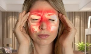 Blonde woman with sinus pressure holding hands to her temples with infrared marks showing pain locations.